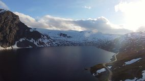 Aerial drone view mountain road by the lake in Norway. Scandinavian journey with beautiful landscape stock footage