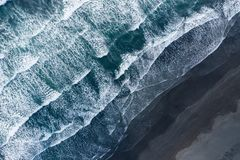 Aerial Drone View Of Ocean Waves Washing Black Sand Beach, Iceland Stock Photo