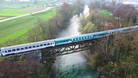 Aerial drone view of public train passing old metal bridge stock video footage