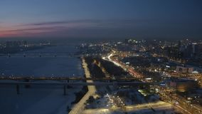 Aerial drone view of river bank of snow covered night city with traffic jams. stock footage