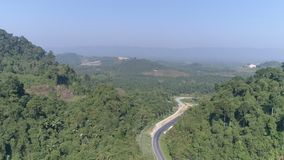 Aerial view of road among beautiful rain forest. Aerial drone view of road among beautiful rain forest in summer day. Travel concept stock footage