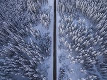 Aerial drone view of road in idyllic winter landscape. Street running through the nature from a birds eye view. stock photo