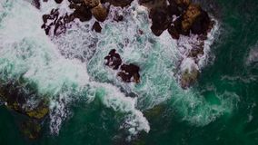 Aerial drone view of rocky coastline with crashing sea waves.  stock footage