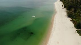 Aerial drone view to green ocean with small boat and white sandy coast with tropical plants in Thailand. Cocunut Palms. On exotic beach stock video