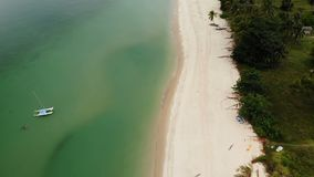 Aerial drone view to green ocean with small boat and white sandy coast with tropical plants in Thailand. Cocunut Palms. On exotic beach stock footage
