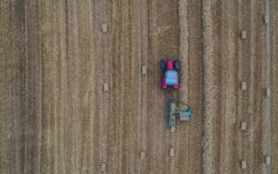 Aerial drone view of tractor working in a wheat field creating straw bales, haystacks stock image