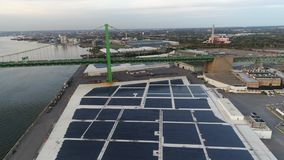 Aerial drone view of waterfront warehouse covered in solar panels stock video