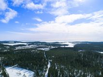 Aerial drone view of a winter landscape. Snow covered forest and lakes from the top. Sunrise in nature from a birds eye view. Aerial drone view of a winter Stock Photo