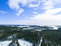 Aerial drone view of a winter landscape. Snow covered forest and lakes from the top. Sunrise in nature from a birds eye view. Aerial drone view of a winter Royalty Free Stock Photography