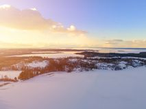 Aerial drone view of a winter landscape. Snow covered forest and lakes from the top. Sunrise in nature from a birds eye view. Aer stock image