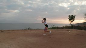 Aerial view of woman exercising on sea shore cliff at sunrise
