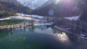 AERIAL: Ducks swimming on idyllic highland lake between the snowy mountains stock footage