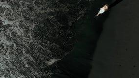 aerial Eine Ansicht von einem Brummen auf einem jungen M?dchen auf einem Strand mit schwarzem vulkanischem Sand, Teneriffa, Kanar stock video footage