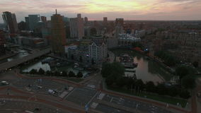 Aerial evening scene of Rotterdam, Netherlands. Aerial - Cityscape of Rotterdam with view to the White House, Cube Houses, Markthal and transport traffic stock video