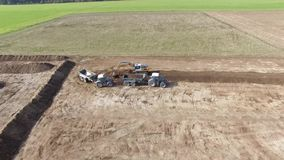 Aerial of excavator loading the tipper truck on an big agriculture field. 4k stock video