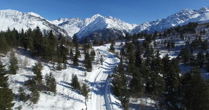 Aerial filming of a winter road among the mountains. Erial photography of the snow-covered road in the mountains of the cargo on a clear day stock video footage