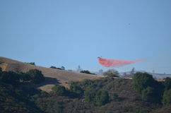 Aerial Firefighting Aircraft Dropping Fire Retardant. This aerial firefighting aircraft drop a load of fire retardant on the wildfire Royalty Free Stock Photo