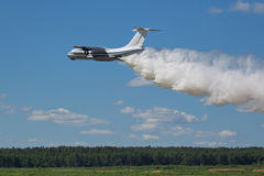 Aerial firefighting. Flying aerial firefighting pour water over the fire royalty free stock photo