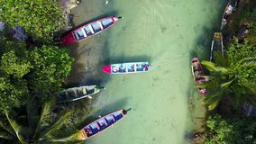 Aerial of fishing boats on White River, Ocho Rios, Jamaica. Aerial shot of White River, Ocho Rios, Jamaica with 4 colorful fishing boat moored in a small fishing stock footage