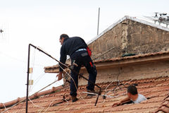Aerial fitter. A antenna fitter in action on a roof during his job Stock Photography