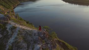Aerial flight above couple in love kissing in cliff edge near water. Woman in amazing red dress. Man in black. Sunset. 4K stock footage