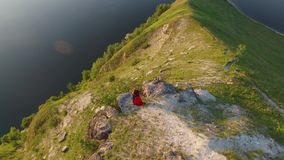 Aerial flight above couple in love standing in cliff edge near water. Woman in amazing red dress. Man in black. Sunset. 4K stock video footage