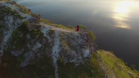 Aerial flight above couple in love standing in cliff edge near water. Woman in amazing red dress. Man in black. Sunset. 4K stock footage