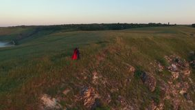 Aerial flight above couple in love walking on the river bank edge. Woman in amazing red dress. Man in black. Sunset. 4K stock footage