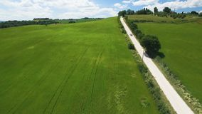 Aerial flight over the field along the rural road. In the Background of blue sky and clouds. Italy, Tuscany. Aerial flight over the field along the rural road stock footage