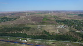 Aerial flight above green meadows and windmills