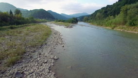 Aerial: flight above mountain river in Carpathians stock video footage