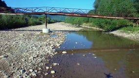 Aerial: flight above mountain river in Carpathians. Drone flight under the bridge. Aerial: flight above mountain river in Carpathians. Drone flight under the stock video footage