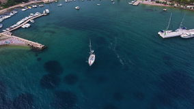 Aerial: Flight above the sail boat on clear blue water after leaving marina stock video footage