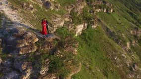Aerial flight around couple in love standing in cliff edge near water. Woman in amazing red dress. Man in black. Sunset. HD stock footage