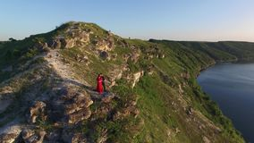 Aerial flight away from couple in love standing in cliff edge near water. Woman in amazing red dress. Man in black. Sunset. 4K stock video footage