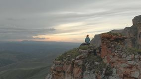 Aerial - flight backward past sitting on vacation adult woman with a backpack sits and rests of the rock at the foot of. The epic plateau at sunset. View from stock footage