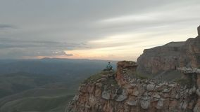 Aerial - flight forward past sitting on vacation adult woman with a backpack sits and rests of the rock at the foot of. The epic plateau at sunset. View from stock video