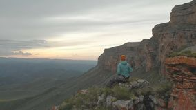Aerial - flight forward past sitting on vacation adult woman with a backpack sits and rests of the rock at the foot of. The epic plateau at sunset. View from stock video footage