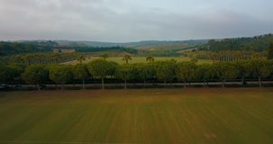 Aerial flight, low altitude, over hills and polo fields at sunset stock video