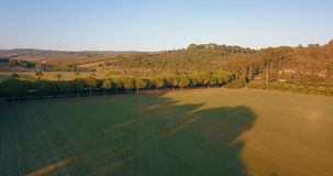 Aerial flight, low altitude, over hills and polo fields at sunset stock video footage