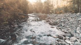 Aerial Flight: mountain river in autumn forest. Aerial Drone Flight above mountain river in autumn forest. Water flows through cascades massive boulders. Sunset stock footage