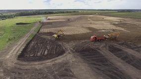 Aerial flight over earth moving machines and construction site. Construction crews prepare a site for a building . Circular flight over the field where the stock footage