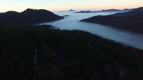Aerial flight over fog forest with mountain range on background stock video