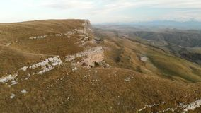 AERIAL: Flight over a high rock cliff, revealing a view of the pass in russia in the northern Caucasus. Aerial. Photography of the road in the setting sun stock video footage