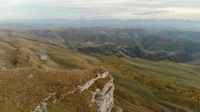 AERIAL: Flight over a high rock cliff, revealing a view of the pass in russia in the northern Caucasus. Aerial. Photography of the road in the setting sun stock video