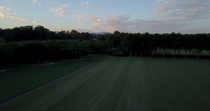 Aerial flight over hills and polo field at sunset. Aerial drone footage over hills and polo fields at sunset, camera descending and moving forward stock footage