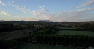 Aerial flight over hills and polo field at sunset. Aerial drone footage over hills and polo fields at sunset, camera descending and moving forward stock video