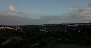 Aerial flight over hills and polo field at sunset. Aerial drone footage over hills and polo fields at sunset, camera descending and moving right stock footage