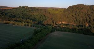 Aerial flight over hills and polo field at sunset. Aerial drone footage over hills and polo fields at sunset, camera descending and tilting up stock video