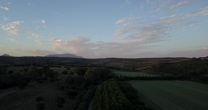 Aerial flight over hills and polo field at sunset. Aerial drone footage over hills and polo fields at sunset, camera forward and up stock video footage